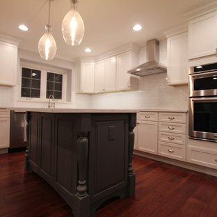 Inspiration for a large cottage l-shaped medium tone wood floor eat-in kitchen remodel in Philadelphia with a farmhouse sink, shaker cabinets, white cabinets, white backsplash, stainless steel appliances, an island, quartzite countertops and subway tile backsplash