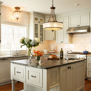 Inspiration for a mid-sized traditional u-shaped open plan kitchen in St Louis with soapstone benchtops, recessed-panel cabinets, white splashback, subway tile splashback, stainless steel appliances, an undermount sink, grey cabinets, medium hardwood floors and with island.