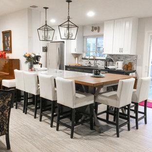 サクラメントの小さいコンテンポラリースタイルのおしゃれなキッチン (アンダーカウンターシンク、レイズドパネル扉のキャビネット、白いキャビネット、メタリックのキッチンパネル、ボーダータイルのキッチンパネル、シルバーの調理設備の、磁器タイルの床、ベージュの床、グレーのキッチンカウンター) の写真