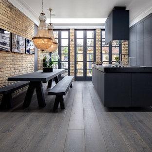 Modelo de cocina comedor lineal, ecléctica, de tamaño medio, con armarios con paneles lisos, puertas de armario negras, suelo de madera oscura, una isla, suelo marrón y electrodomésticos con paneles