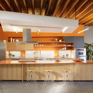 Idee per una cucina design con lavello stile country, ante lisce, ante in legno chiaro, paraspruzzi arancione, paraspruzzi a finestra, elettrodomestici in acciaio inossidabile, pavimento in cemento, isola, pavimento grigio e top arancione