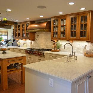 Lantlig inredning av ett stort kök, med en rustik diskho, luckor med profilerade fronter, bruna skåp, marmorbänkskiva, vitt stänkskydd, stänkskydd i keramik, rostfria vitvaror, tegelgolv, en köksö och rött golv
