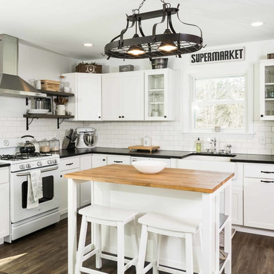 Inspiration for a mid-sized farmhouse l-shaped vinyl floor and brown floor kitchen remodel in Portland Maine with a farmhouse sink, shaker cabinets, white cabinets, granite countertops, white backsplash, subway tile backsplash, white appliances and an island
