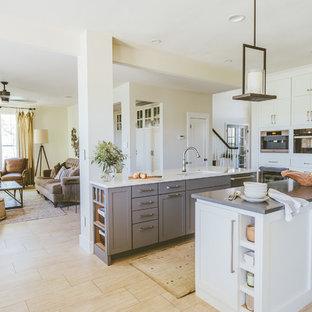 Klassisk inredning av ett stort kök, med skåp i shakerstil, vita skåp, bänkskiva i koppar, rostfria vitvaror, klinkergolv i porslin, en undermonterad diskho, flera köksöar, grått stänkskydd, stänkskydd i glaskakel och beiget golv