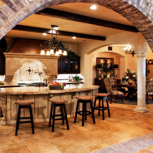 Design ideas for a large mediterranean l-shaped open plan kitchen in Austin with a farmhouse sink, raised-panel cabinets, dark wood cabinets, granite benchtops, beige splashback, ceramic splashback, stainless steel appliances, ceramic floors, with island and beige floor.