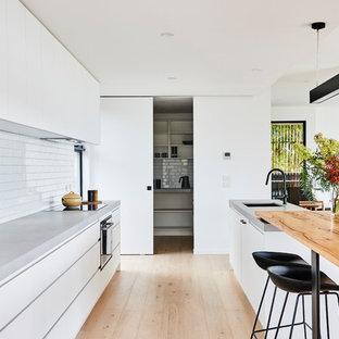 ジーロングの中サイズのモダンスタイルのおしゃれなキッチン (ダブルシンク、フラットパネル扉のキャビネット、白いキャビネット、木材カウンター、白いキッチンパネル、サブウェイタイルのキッチンパネル、黒い調理設備、淡色無垢フローリング、茶色い床、グレーのキッチンカウンター) の写真