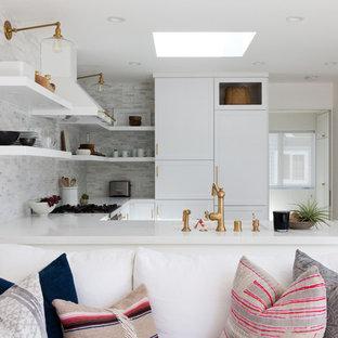 ロサンゼルスの中サイズのビーチスタイルのおしゃれなキッチン (ドロップインシンク、落し込みパネル扉のキャビネット、白いキャビネット、大理石カウンター、白いキッチンパネル、磁器タイルのキッチンパネル、白い調理設備、淡色無垢フローリング、アイランドなし) の写真