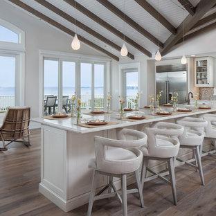Idee per una grande cucina stile marino con ante bianche, top in quarzite, paraspruzzi multicolore, elettrodomestici in acciaio inossidabile, isola, ante di vetro, pavimento in legno massello medio, lavello sottopiano, paraspruzzi con piastrelle a mosaico e pavimento marrone