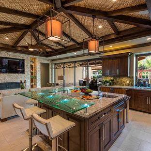 Immagine di una cucina tropicale con ante con riquadro incassato, ante in legno bruno, top in granito, paraspruzzi verde, paraspruzzi con piastrelle di vetro, pavimento in travertino e isola