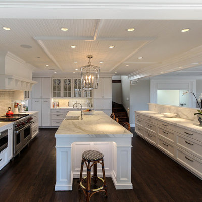 Open concept kitchen - large transitional u-shaped dark wood floor and brown floor open concept kitchen idea in Other with stainless steel appliances, an island, a farmhouse sink, shaker cabinets, white cabinets, white backsplash, stone tile backsplash and marble countertops