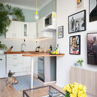 Design ideas for a small scandi l-shaped open plan kitchen in London with a submerged sink, shaker cabinets, white cabinets, wood worktops, white splashback, ceramic splashback, stainless steel appliances, laminate floors and a breakfast bar.