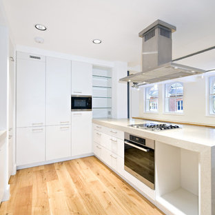 Mid-sized contemporary eat-in kitchen inspiration - Example of a mid-sized trendy u-shaped light wood floor eat-in kitchen design in London with a peninsula, an integrated sink, flat-panel cabinets, white cabinets, concrete countertops, white backsplash, glass sheet backsplash and stainless steel appliances