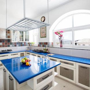 Imagen de cocina en L, mediterránea, con fregadero bajoencimera, armarios con paneles empotrados, salpicadero multicolor, una isla, suelo gris y encimeras azules