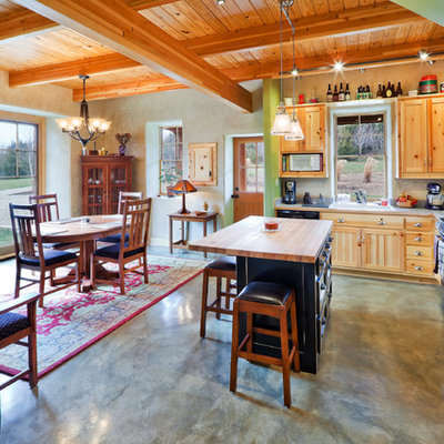 Inspiration for a small rustic l-shaped concrete floor open concept kitchen remodel in Kansas City with black appliances, wood countertops, a double-bowl sink, shaker cabinets, light wood cabinets, gray backsplash and an island