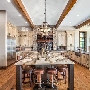シカゴのラスティックスタイルのおしゃれなキッチン (エプロンフロントシンク、レイズドパネル扉のキャビネット、中間色木目調キャビネット、黒いキッチンパネル、シルバーの調理設備、無垢フローリング、茶色い床、黒いキッチンカウンター) の写真