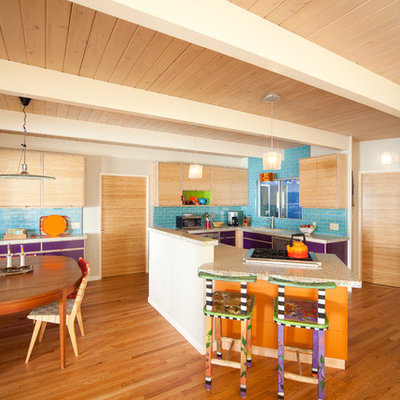 Eat-in kitchen - mid-sized eclectic u-shaped medium tone wood floor and brown floor eat-in kitchen idea in San Luis Obispo with flat-panel cabinets, light wood cabinets, subway tile backsplash, stainless steel appliances, an undermount sink, blue backsplash, a peninsula, recycled glass countertops and multicolored countertops