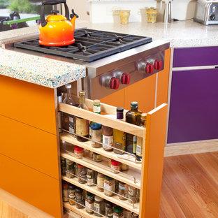 Exempel på ett mellanstort eklektiskt flerfärgad flerfärgat kök, med släta luckor, rostfria vitvaror, en undermonterad diskho, skåp i ljust trä, blått stänkskydd, stänkskydd i tunnelbanekakel, mellanmörkt trägolv, en halv köksö, brunt golv och bänkskiva i återvunnet glas