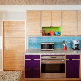 Exempel på ett mellanstort eklektiskt flerfärgad flerfärgat kök, med rostfria vitvaror, släta luckor, skåp i ljust trä, stänkskydd i tunnelbanekakel, en undermonterad diskho, blått stänkskydd, mellanmörkt trägolv, en halv köksö, brunt golv och bänkskiva i återvunnet glas