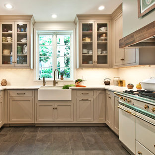 This is an example of a mid-sized transitional u-shaped kitchen in Nashville with a farmhouse sink, beige cabinets, quartzite benchtops, white splashback, ceramic splashback, stainless steel appliances, porcelain floors, no island and glass-front cabinets.
