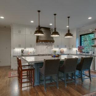 ナッシュビルの中サイズのシャビーシック調のおしゃれなキッチン (アンダーカウンターシンク、シェーカースタイル扉のキャビネット、白いキャビネット、御影石カウンター、白いキッチンパネル、セラミックタイルのキッチンパネル、シルバーの調理設備の、無垢フローリング、茶色い床、グレーのキッチンカウンター) の写真