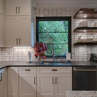 ナッシュビルの中サイズのシャビーシック調のおしゃれなキッチン (アンダーカウンターシンク、シェーカースタイル扉のキャビネット、白いキャビネット、御影石カウンター、白いキッチンパネル、セラミックタイルのキッチンパネル、シルバーの調理設備、無垢フローリング、茶色い床、グレーのキッチンカウンター) の写真