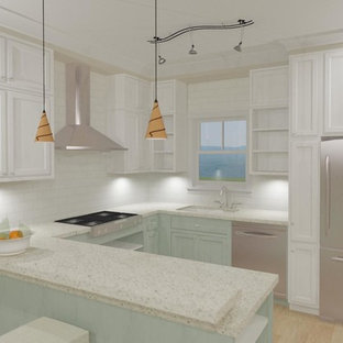 This is an example of a mid-sized beach style u-shaped open plan kitchen in Charleston with an undermount sink, recessed-panel cabinets, turquoise cabinets, recycled glass benchtops, white splashback, subway tile splashback, stainless steel appliances, medium hardwood floors and a peninsula.