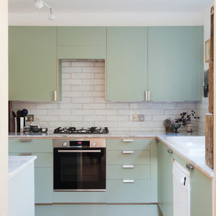 Design ideas for a small contemporary u-shaped separate kitchen in London with a double-bowl sink, flat-panel cabinets, green cabinets, quartzite benchtops, grey splashback, ceramic splashback, white appliances, cork floors, no island, brown floor and grey benchtop.