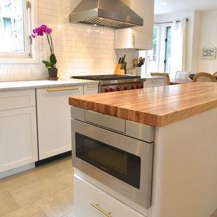 デンバーの小さいシャビーシック調のおしゃれなキッチン (シングルシンク、シェーカースタイル扉のキャビネット、白いキャビネット、木材カウンター、白いキッチンパネル、セラミックタイルのキッチンパネル、シルバーの調理設備、磁器タイルの床、グレーの床、白いキッチンカウンター) の写真