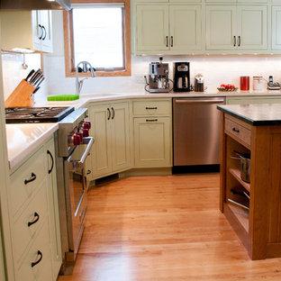Imagen de cocina en L, de estilo americano, grande, abierta, con fregadero bajoencimera, armarios con rebordes decorativos, encimera de esteatita, salpicadero blanco, salpicadero de azulejos tipo metro, electrodomésticos de acero inoxidable, suelo de madera clara y una isla