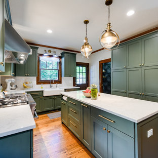 Mid-sized arts and crafts l-shaped kitchen in Oklahoma City with a farmhouse sink, shaker cabinets, green cabinets, quartz benchtops, yellow splashback, ceramic splashback, stainless steel appliances, medium hardwood floors, with island, brown floor and white benchtop.