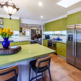 Photo of a medium sized bohemian kitchen in Melbourne with a built-in sink, flat-panel cabinets, green cabinets, laminate countertops, multi-coloured splashback, ceramic splashback, stainless steel appliances, ceramic flooring and an island.