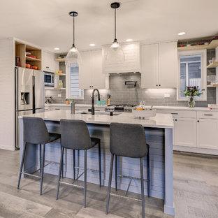 Inspiration för ett litet vintage vit vitt kök, med en undermonterad diskho, skåp i shakerstil, vita skåp, bänkskiva i kvarts, grått stänkskydd, stänkskydd i keramik, rostfria vitvaror, mellanmörkt trägolv, en köksö och grått golv