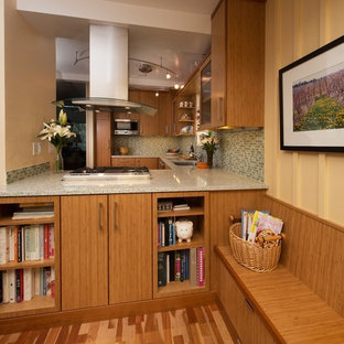 This is an example of a small contemporary u-shaped eat-in kitchen in San Francisco with an undermount sink, flat-panel cabinets, medium wood cabinets, recycled glass benchtops, green splashback, glass tile splashback, stainless steel appliances, medium hardwood floors and a peninsula.