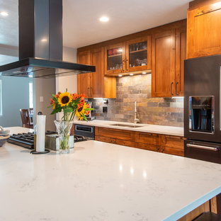 This is an example of a large country l-shaped eat-in kitchen in Denver with an undermount sink, shaker cabinets, brown cabinets, quartz benchtops, multi-coloured splashback, slate splashback, stainless steel appliances, medium hardwood floors, with island, brown floor and white benchtop.
