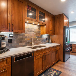 Large country l-shaped eat-in kitchen in Denver with an undermount sink, shaker cabinets, brown cabinets, quartz benchtops, multi-coloured splashback, slate splashback, stainless steel appliances, medium hardwood floors, with island, brown floor and white benchtop.