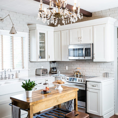 Enclosed kitchen - large rustic l-shaped dark wood floor and brown floor enclosed kitchen idea in Other with a farmhouse sink, white cabinets, stainless steel appliances, an island, recessed-panel cabinets, quartzite countertops, gray backsplash and subway tile backsplash