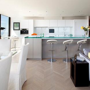 Immagine di una cucina ad ambiente unico minimal con ante lisce, paraspruzzi con lastra di vetro, ante bianche, paraspruzzi bianco, top in vetro e elettrodomestici da incasso