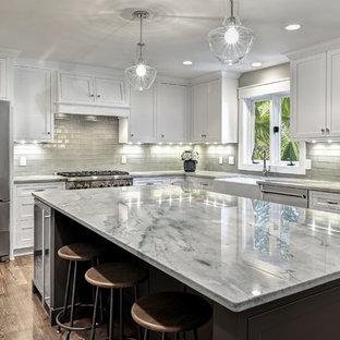 Inspiration för stora klassiska u-kök, med en rustik diskho, skåp i shakerstil, vita skåp, marmorbänkskiva, grått stänkskydd, rostfria vitvaror, mörkt trägolv, en köksö och brunt golv