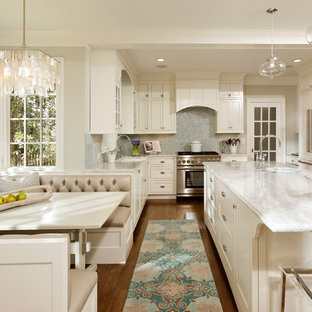 Traditional eat-in kitchen pictures - Elegant l-shaped eat-in kitchen photo in DC Metro with stainless steel appliances, recessed-panel cabinets, white cabinets, quartzite countertops, blue backsplash and glass tile backsplash
