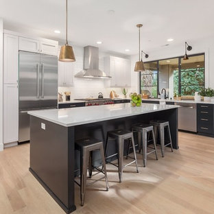 Large transitional eat-in kitchen ideas - Large transitional l-shaped light wood floor and brown floor eat-in kitchen photo in Seattle with shaker cabinets, white backsplash, stainless steel appliances, an island, white countertops, an undermount sink, granite countertops and porcelain backsplash