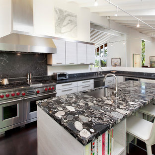 Photo of a large contemporary u-shaped kitchen in San Francisco with flat-panel cabinets, grey cabinets, granite benchtops, black splashback, stone slab splashback, stainless steel appliances, dark hardwood floors, with island, black benchtop, an undermount sink and brown floor.