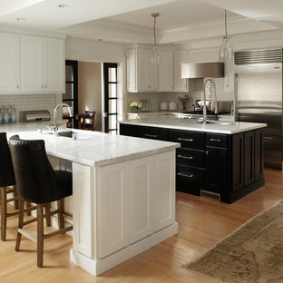 Inspiration for a contemporary u-shaped eat-in kitchen remodel in San Francisco with subway tile backsplash, stainless steel appliances, an undermount sink, shaker cabinets, white cabinets, marble countertops and white backsplash