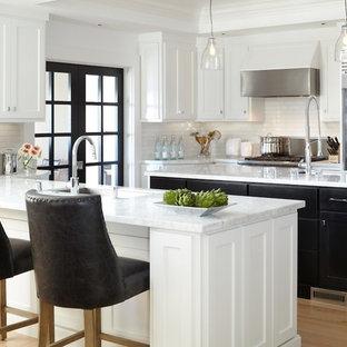 Foto di una cucina ad U contemporanea con elettrodomestici in acciaio inossidabile, lavello sottopiano, ante in stile shaker, ante nere, top in marmo, paraspruzzi bianco e paraspruzzi con piastrelle diamantate
