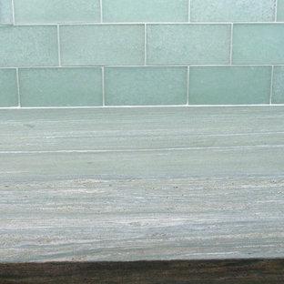 Ejemplo de cocina en L, clásica, de tamaño medio, abierta, con fregadero encastrado, armarios estilo shaker, puertas de armario blancas, salpicadero gris, suelo de madera clara, una isla y encimeras turquesas