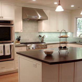 This is an example of a mid-sized traditional l-shaped open plan kitchen in San Francisco with a drop-in sink, shaker cabinets, white cabinets, green splashback, light hardwood floors, with island, granite benchtops, glass tile splashback, stainless steel appliances, brown floor and green benchtop.