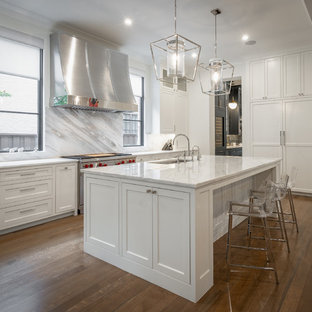 Example of a transitional l-shaped brown floor kitchen design in Dallas with an undermount sink, beaded inset cabinets, white cabinets, stainless steel appliances, an island and white countertops