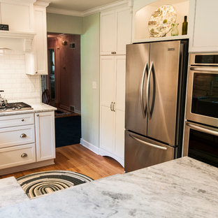 Small transitional enclosed kitchen ideas - Inspiration for a small transitional u-shaped medium tone wood floor enclosed kitchen remodel in Milwaukee with a farmhouse sink, shaker cabinets, white cabinets, granite countertops, white backsplash, subway tile backsplash, stainless steel appliances and a peninsula