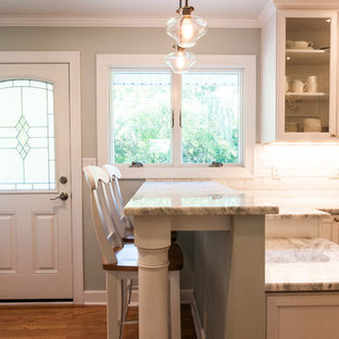 Small transitional enclosed kitchen inspiration - Example of a small transitional u-shaped medium tone wood floor enclosed kitchen design in Milwaukee with a farmhouse sink, shaker cabinets, white cabinets, granite countertops, white backsplash, subway tile backsplash, stainless steel appliances and a peninsula