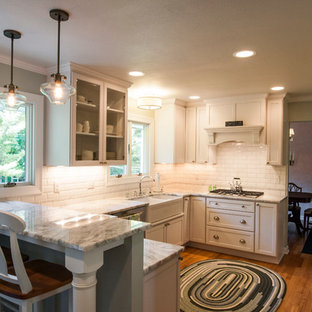 Small transitional enclosed kitchen designs - Small transitional u-shaped medium tone wood floor enclosed kitchen photo in Milwaukee with a farmhouse sink, shaker cabinets, white cabinets, granite countertops, white backsplash, subway tile backsplash, stainless steel appliances and a peninsula