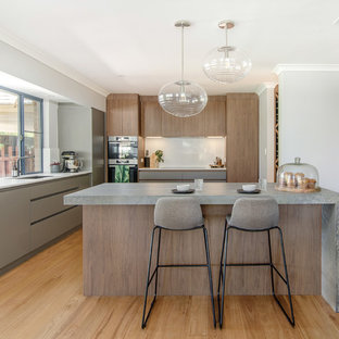 Photo of a contemporary l-shaped kitchen in Perth with an undermount sink, flat-panel cabinets, medium wood cabinets, stainless steel appliances, medium hardwood floors, with island, brown floor and grey benchtop.